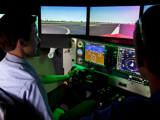 Chandler Hunte, 17, a senior at Evangelical Christian School in Fort Myers, trains using a Redbird flight simulator at Paragon Flight School under the supervision of chief flight instructor Jeffrey Wolf Wednesday afternoon (10/21/15).
