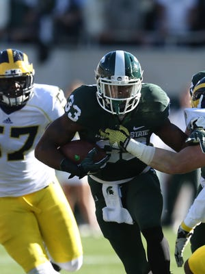 Michigan State RB Jeremy Langford runs by Michigan defenders during the second quarter on Oct. 25, 2014, at Spartan Stadium.