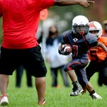 A Kappa Express coach points the correct way for an Express running back to run in game action against the Warriors in 7U Lansing Football League game Saturday, Sept. 24, 2016 at the Southside Community Center in Lansing.