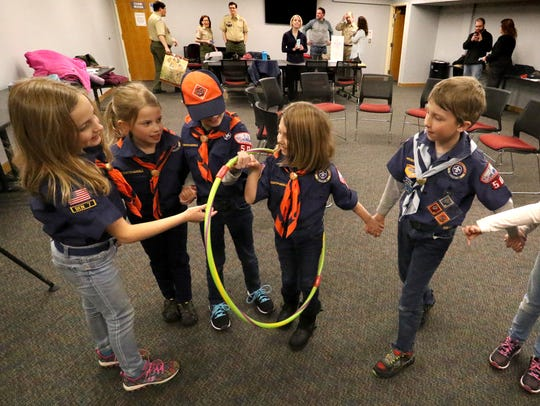 """Cubs from Den 7, Pack 505 play and ice breaking game of passing a hoop between them without letting hands go at the Greendale Library on Feb. 8. Den 7 is one of two new girl Cub Scout dens to form in the area. Boy Scouts of America will drop """"Boy"""" from the name of its signature program and will be called Scout BSA."""