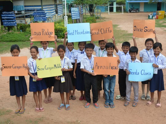 Cambodian students hold up signs of the schools raising