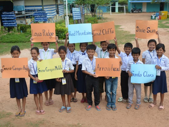 88029390db5e Cambodian students hold up signs of the schools raising