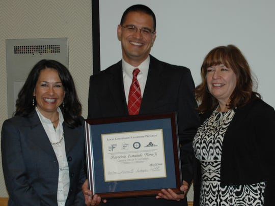 Sgt. Pat Flores, director of the city of Farmington's Criminal Justice Training Authority, center, recently graduated from the Local Government Leadership Program.