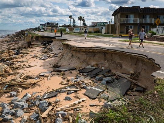 Pedestrians survey a section of State Road A1A in Flagler County damaged by erosion when Hurricane Matthew plowed up the east coast of Florida in October.
