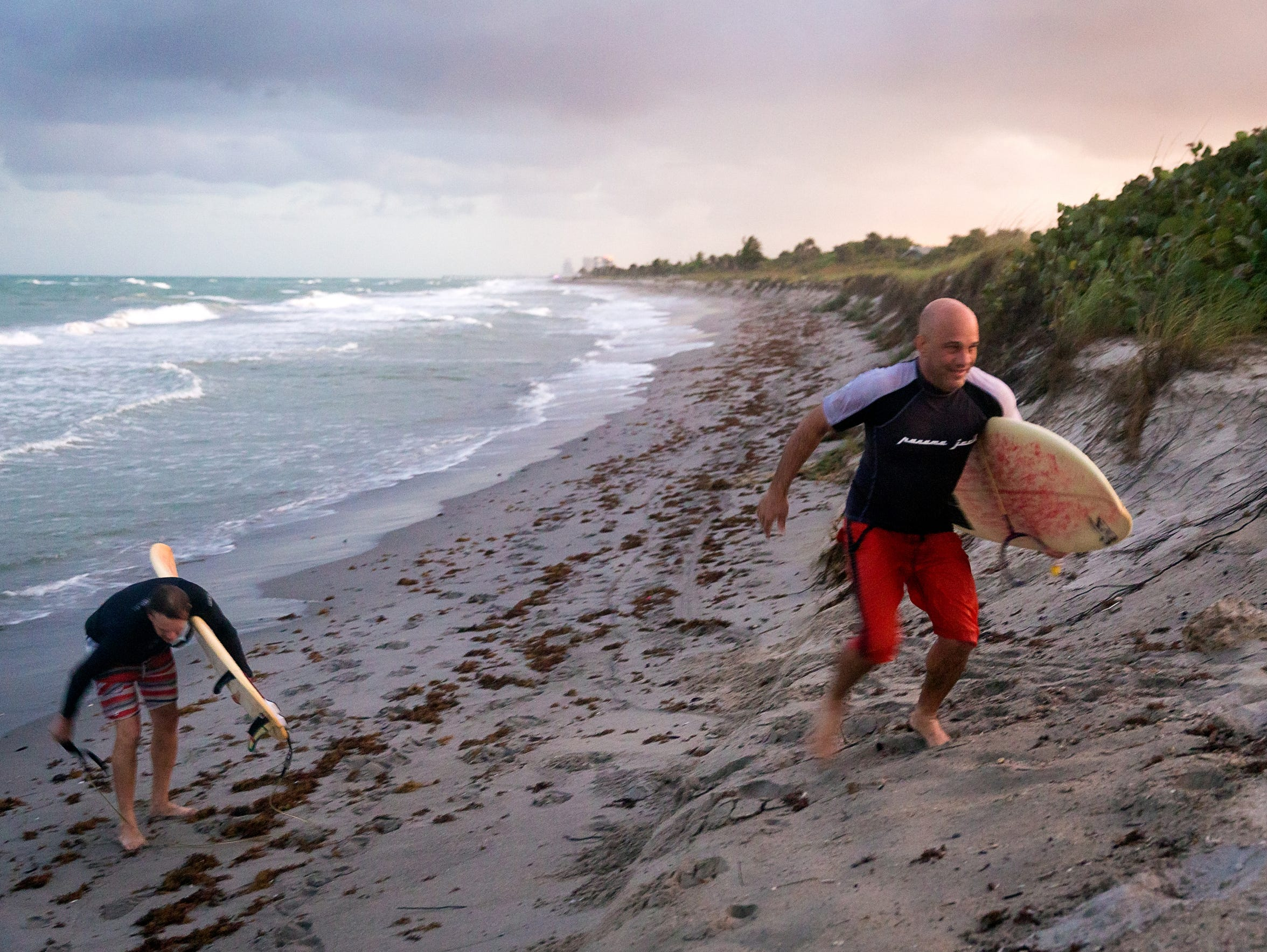 Surfers climb beach erosion cliffing as they are kicked
