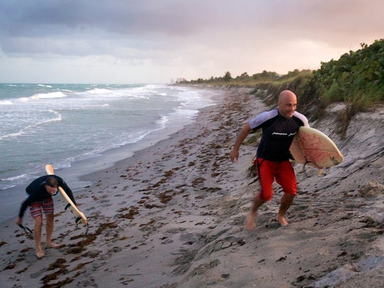 Surfers climb beach erosion cliffing as they are kicked out by park officials at dusk of Dr. Von D. Mizell-Eula Johnson State Park (formerly known as John U. Lloyd Beach State Park) in October 2015. The state park is located to the south of the Port Everglades inlet in Broward County where it is suffering from critical erosion issues caused by the inlet's blockage of the natural north-to-south flow of sand along Florida's coastlines.
