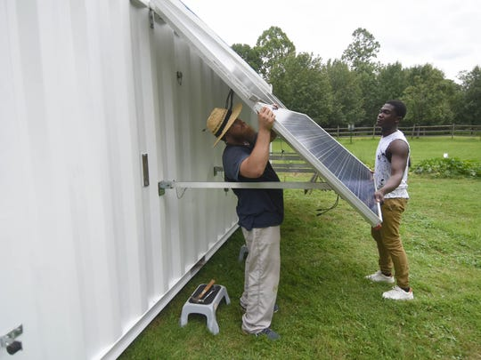 Nick Horvath and Alexander Asante, members of BoxPower Inc., install a hybrid renewable energy system  that would bring power to the Ramapough Lenape at the Mahwah campground.