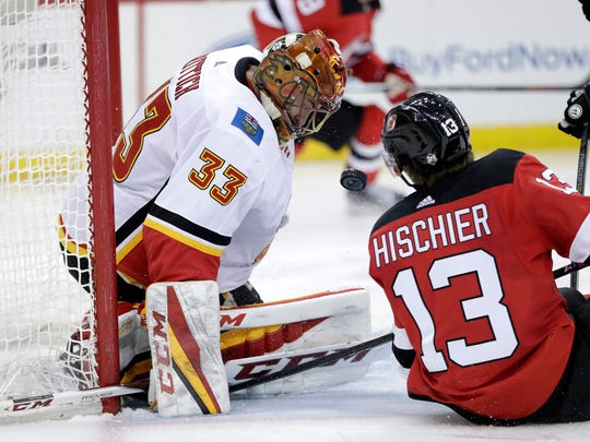 Calgary Flames goaltender David Rittich (33), of the Czech Republic, blocks a shot as New Jersey Devils center Nico Hischier (13), of Switzerland, falls to the ice during the second period of an NHL hockey game, Thursday, Feb. 8, 2018, in Newark, N.J.