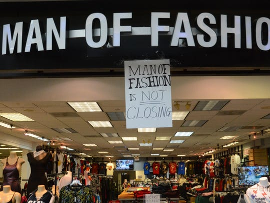 Man of Fashion business owner Taha Qadi put up a sign to let shoppers know he is still open, one of the few remaining tenants after mall management terminated month-to-month leases.