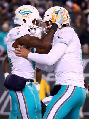 Matt Moore celebrates with Jarvis Landry after scoring a touchdown in the third quarter.