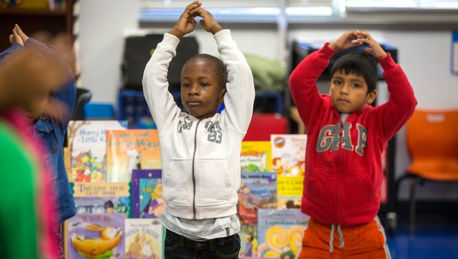 Alisha Sinclair's kindergarten class at Edmunds Academy in Des Moines practices yoga at the beginning of the school day, Oct. 13, 2016. Here, Success Tarlue, left, and Jonathan Pineda-Rodriguez practice yoga.