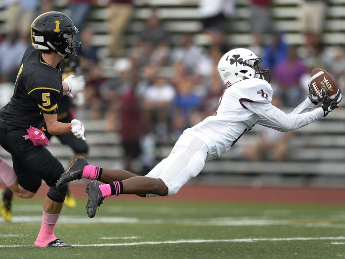 Aquinas' Kobe McNair, right, makes a diving catch in