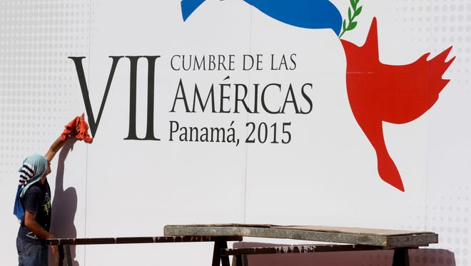 A worker gives the finishing touches to a wall announcing the upcoming Summit of the Americas outside of the Atlapa Convention Center in Panama City, on April 6, 2015.