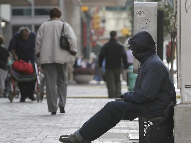A panhandler sits along Illinois Street in Downtown Indianapolis.