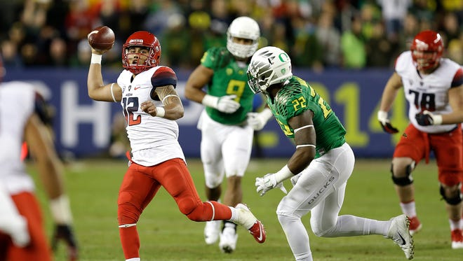 Arizona quarterback Anu Solomon, left, passes under pressure from Oregon's Derrick Malone (22) during the first half of the Pac-12 championship on Friday, Dec. 5, 2014, in Santa Clara, Calif.