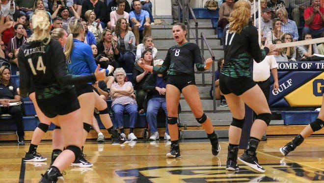 Catholic's Terra Warrington (8) celebrates after smashing a point in against Gulf Breeze at Gulf Breeze High School on Tuesday, Sept. 12, 2017. The Crusaders beat the Dolphins and remain undefeated.