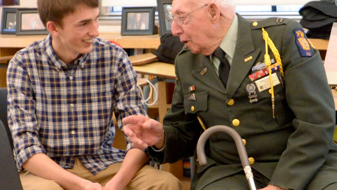 World War II Harold Kummer, US Army mortarman, right, shares a story from WWII with history student Ben Thompson at Lincoln High School.