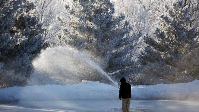 Dean Lorenzen, a Sioux Falls Parks and Recreation park caretaker, sprays water over the ice skating rink while making ice in McKennan Park on Monday, Jan. 4, 2016.