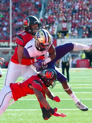 Washington Huskies wide receiver John Ross (1) scores a touchdown as he is tackled by Utah Utes defensive back Jordan Fogal (13) and linebacker Kavika Luafatasaga (55) during the first half at Rice-Eccles Stadium.