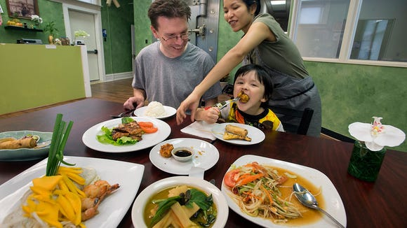 From the left, Tom Ryan, his wife Aree and son Satapawn, age 4, dig into the sample dishes after offering up the dishes for the photographer to shoot at Krua Thai Cafe at 45 East Main Street in Dallastown, Wednesday July 8, 2015. A vault from the former bank is in the dining room.  Paul Kuehnel - York Daily Record/ Sunday News