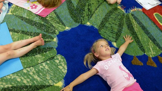 Gwendolyn Jahn, 3, relaxes on the floor during the final part of a yoga class for kids taught by Debora Hutchison (not pictured) at the Brown County East Branch Library.