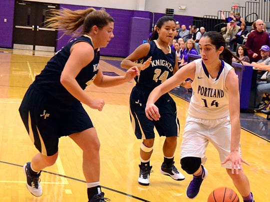 Portland High junior Mackenzie Trouten (14) dribbles to the basket as Pope John Paul II seniors Windee Johnson and Mercedes Smith (24) converge during first-quarter action. Trouten scored a career-high 17 points in the Lady Panthers' 52-37 victory on Tuesday evening.