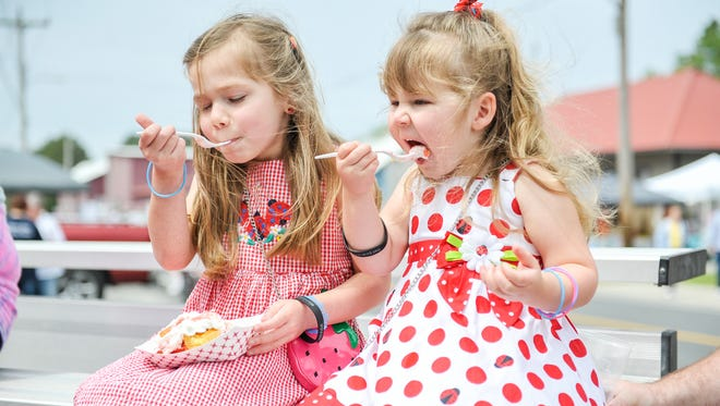 Isablella, 5, (left) and her sister, Sophia McHenry, 2, of Crisfield share a fresh strawberry shortcake during the annual Somerset Strawberry Festival in Downtown Marion Station.