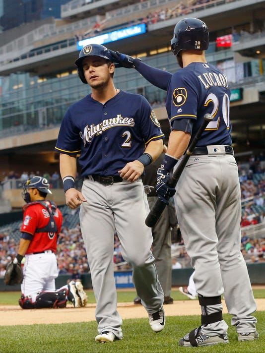 Milwaukee Brewers' Jonathan Lucroy, right, gives Scooter Gennett a congratulatory tap on the helmet after he scored on a hit by Ryan Braun off Minnesota Twins pitcher Phil Hughes in the first inning of a baseball game Monday, April 18, 2016, in Minneapolis. (AP Photo/Jim Mone)