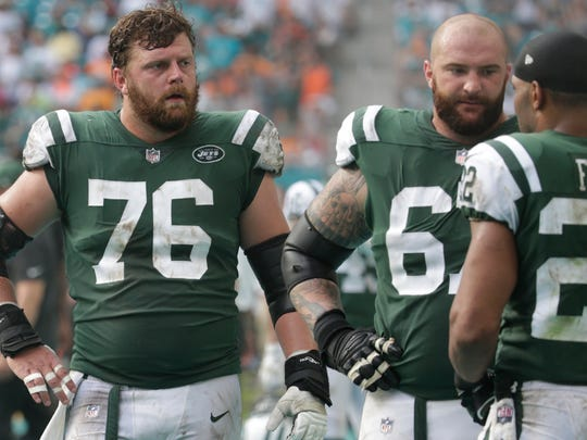 New York Jets center Wesley Johnson (76) and offensive guard Brian Winters (67), listens to running back Matt Forte (22) on the sidelines,during the second half of an NFL football game against the Miami Dolphins, Sunday, Oct. 22, 2017, in Miami Gardens, Fla.