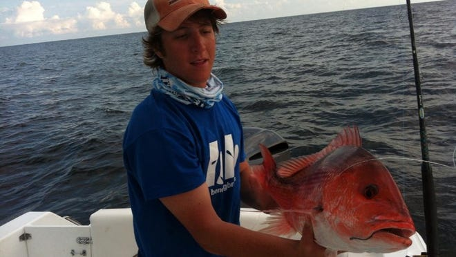 Local angler Keith Morrison shows off a red snapper he caught last year while fishing in Florida state waters.
