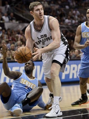 San Antonio Spurs center Aron Baynes takes the ball away from the Denver Nuggets on April 3, 2015, in San Antonio.