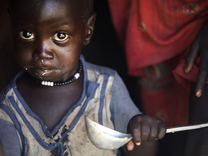 A boy eats out of a ladle at his home in Ngop in South