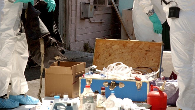 The contents of a methamphetamine manufacturing lab rest on the driveway of the MRC motel, next to the Rail City Casino, as law enforcement agents catalog the findings in 2004.