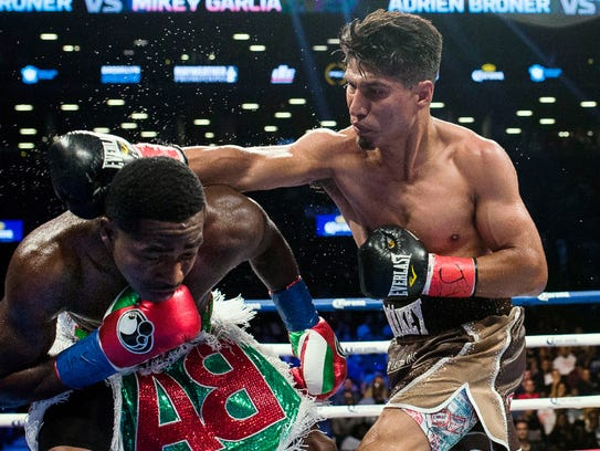 Mikey Garcia, right, throws a right hand at Adrien