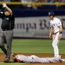 Second base umpire Jerry Layne calls for time as Boston Red Sox second baseman Dustin Pedroia is injured after colliding with Tampa Bay Rays' Logan Forsythe during the second inning of a baseball game Saturday, Aug. 30, 2014, in St. Petersburg, Fla. Pedroia left the game.