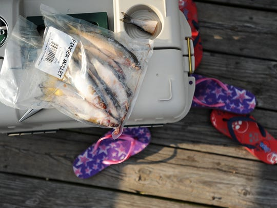 Brayden Dycus and Lynnze Ruland of Virginia Beach kicked off their flip-flops near their tackle box while fishing off the Cape Charles Pier.