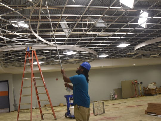 Construction workers at Beech High School have less than three weeks to get the school ready for students. Here a worker installs the bracing for light fixtures in the school's library.