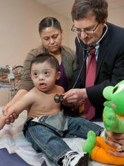 Dr. Mitchel Alpert, a pediatric cardiologist in Brick, examines 22-month-old Drake Vargas, while Drake's mother Ana Perez stands behind.