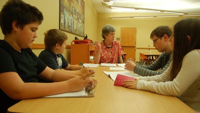 """Author Cathy Travis sits at the head of a table at the Baxter County Library Friday during a discussion on the Constitution. A native of Jonesboro, Travis' book, """"Constitution Translated for Kids,"""" translates the texts of the Constitution to a fifth-grade level."""