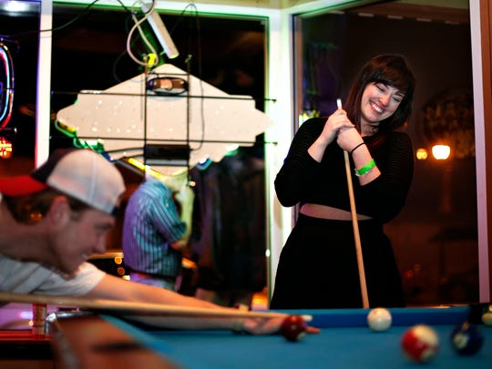 Jennifer Yeager (right) laughs while playing pool with