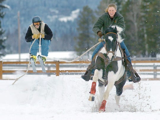 Samantha Young rides her horse, Sly, while pulling Cody McCarthy over a jump while they practice skijoring.