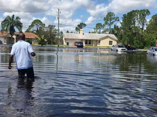 Guima Martial wades to his home on Allman Avenue in Lehigh Acres Tuesday after passing Hurricane Irma at an assisted living facility where his wife works.