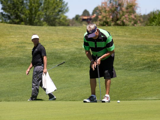 Jesse Mueller, left, watches as Gary Moffitt putts during the second round of the San Juan Open on Friday at the San Juan Country Club in Farmington.