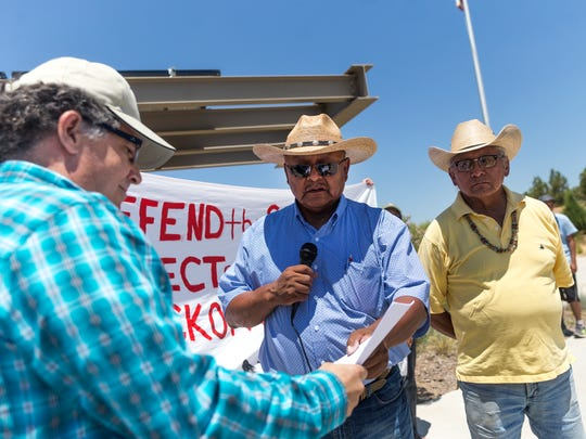 BLM Field Manager Rick Fields, left, receives a letter by Counselor Chapter Community Services Coordinator Samuel Sage protesting the use of hydraulic fracturing in the Greater Chaco Area during a rally at the BLM Field Office in Farmington on Monday.