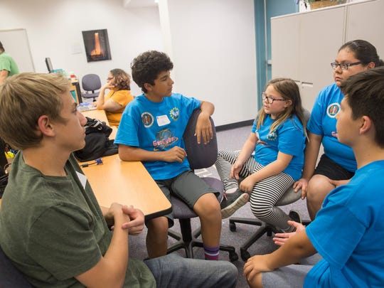 Kody Christensen, left, C.J. Quintana, Gabrielle Litschke, Trinity Castillo and Ayden Connolly discuss a project Wednesda during the GenCyber Summer Training Camp at San Juan College's Quality Center for Business in Farmington.
