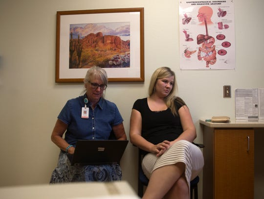 Carol Ewing, a certified nurse midwife talks with her