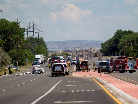 Emergency personnel work the scene of a car crash on Monday on the westbound lane of U.S. 64 in the area of Crawford Mesa east of Farmington.