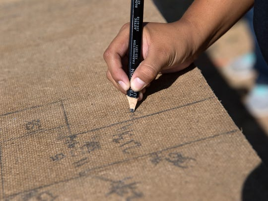 A Navajo YouthBuilders student writes down measurements Thursday during a home renovation project in Shiprock.