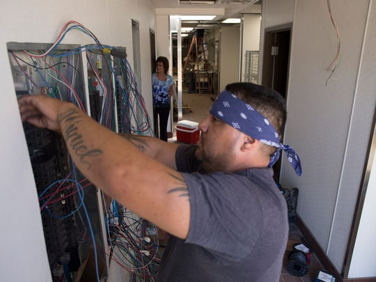 Denny's general manager Eula Holmes, left, watches electrician Omar Loya work on a wiring project Friday at the restaurant's new location in Farmington.