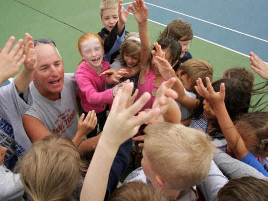 Tennis students gather around Randy Daniels, then-Ankeny